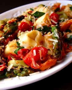 Roasted Tomato and Asparagus Tortellini  2 pints grape tomatoes  1 pound fresh asparagus  5-6 cloves garlic  Olive Oil  Salt and Pepper  1 (24 ounce) package cheese tortellini  1 C chopped spinach  1 T lemon juice (fresh, please)  1 C Parmesan cheese, grated