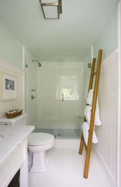 white green blue cottage beachy bathroom design with green blue walls paint color, glossy white beadboard, bamboo ladder towel holder and white bathroom sink vanity with white carrara marble countertops.