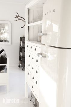 crisp white w/ grey/black toned wood pieces .+ loving the shelving beside the fridge {open top shelves & lots of little drawers .}