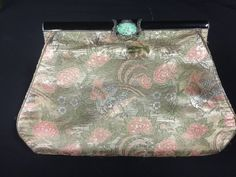 ART DECO SILK EMBROIDERED AVIAN AND BOTANICAL MOTIF CLUTCH WITH ELEGANT BLACK ENAMELED FRAME. THE CLASP HAS A PIERCED JADE CABOCHON AND NUMEROUS MARCASITE STONES. IT IS SIGNED MXDS WITH TWO HALLMARKS, POSSIBLY RHODIUM PLATED. SILK SHOWS SOME WEAR. COMES WITH COIN PURSE AND MEASURES 6X10 INCHES.