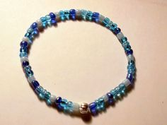 Shades of blue elastic bracelet with a silver tone accent bead.