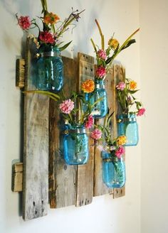 Wooden planks, tea stained and nailed togather with colourful kilner jars screwed on and pretty flowers!