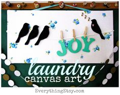 another diy of fabric wrapped around canvas, but with the addition of clothesline and cutout embellishments. love this idea!