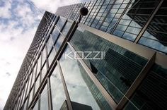 low angle shot of office building against sky. - Low angle view of reflection on office building against cloudy sky.