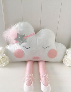 This cloud cushion will look super cute sitting on a little girls bed or shelf. She is a sassy little madam with her sparkly headband and ballerina shoes.  She is completely hand cut from felt. Her face has been hand stitched so each cloud is a little bit unique. She is wearing a pair of handmade white ballerina shoes with white ties. The headband is pink with a super sparkly glitter silver star and finished with a pink feather.  She can be personalised by hand embroidery with any name of…