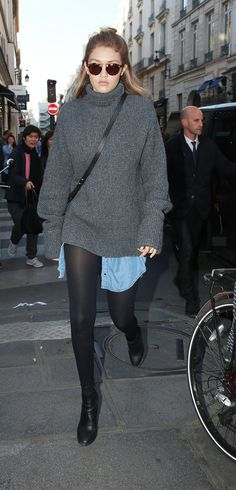 Gigi Hadid looks comfy in an oversize sweater, denim shirt, tights, black boots, and round sunglasses