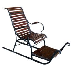 A Charming Swedish Fold Art Wooden and Iron Child's Sled  Sweden  Circa 1880  A charming Swedish folk art wooden and iron child's sled; the slatted wooden chair over a wooden foot rest; applied to an iron frame over iron runners