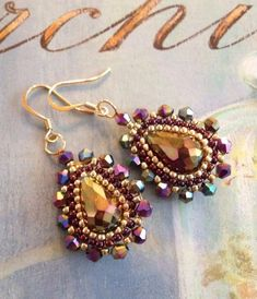 Beadwork earrings made with large metallic purple multicolored crystals and matching 4mm crystal beads accented with metallic gold 11.0 seed beads. If you love big bold bright statement jewelry, just wait until you wear these!!! The gorgeous crystal earrings change from blue to purple to
