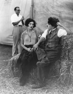 """English comic actor and director Charlie Chaplin (Sir Charles Spencer Chaplin, 1889–1977) seated on straw bales during the filming of """"The Circus"""" with his leading lady Merna Kennedy (1908–1944).© Margaret Chute"""
