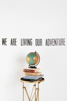 "I don't like that it's a decal, but would be a cute framed quote on a bookshelf next to a painted globe.  ""We are living our adventure"""