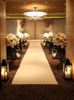 bold black carpet and a massive chandelier with white flowers and accents make this room look magical