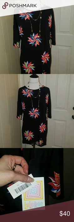 LULAROE IRMA TOP IN SIZE XS * NWT* CUTE IRMA TOP WITH PINWHEEL LIKE DESIGNS AND COOL COLORS THROUGHOUT PRINT WITH BLACK BACKGROUND TO CONTRAST:) BRAND NEW WITH TAGS ATTACHED ** EXTRA SMALL IN SIZE AND SLINKY MATERIAL THAT ALLOWS SOME STRETCHING ROOM IF WANTED) LULAROE BRAND. (NECKLACE NOT FOR SALE ) LuLaRoe Tops Tunics