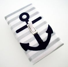 Here is a nautical switch plate / light switch cover made with a navy anchor on a grey and white striped background. Perfect addition to a