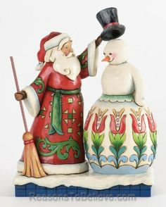 Santa Building Snowman - Share the Spirit-Two of the seasons most beloved images come together in this whimsical scene by Jim Shore. What snowman is complete without his top hat and broom? The colorful patterning on the snowman is Jims version of the German folk art style called fraktur.