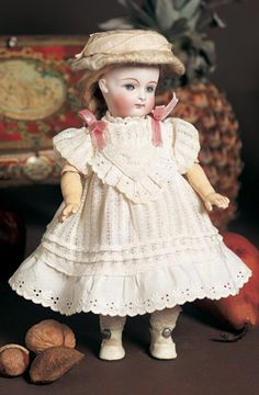 """The pale-complexioned bisque socket head doll has plump facial modelling and nicely blushed cheeks, blue glass sleep eyes, painted lashes, arched feathered brows, accented nostrils and eye corners, closed mouth with pale accented lips, blonde mohair wig in hip-length braids over plaster pate, composition and wooden ball-jointed body with straight wrists. The doll wears antique white cotton dress with drawnwork and embroidery, undergarments, socks, shoes, flannel bonnet. Signed """"111"""". Kestner"""