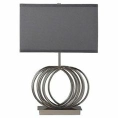 """Pen thank you notes or finish your latest book club read beside this chic table lamp, showcasing a geometric motif with a modern grey box shade.   Product: Table lampConstruction Material: Metal and fabricColor: GreyAccommodates: (1) 150 Watt bulb - not includedDimensions: 22"""" H x 16"""" W"""
