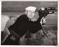 U.S. Navy Photographer's Mate 1st Class N.R. Hertel attached with the 196th Signal Photo Company holds his Bell & Howell 35mm Eyemo 71-Q motion picture camera and a Kodak 35 rangefinder camera around his neck. U.S. Navy and U.S. Army photographer's made up the 196th Signal Photo Company in 1943.