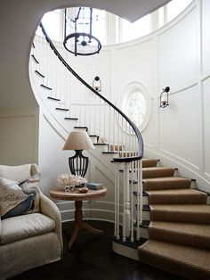 Love the winding staircase in this front hall! Love the dark wood, millwork, and oval window!  via bhg.com