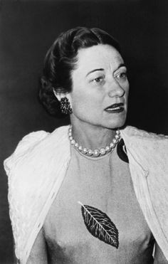 Wallis in the 1950's wearing a leaf motif gown, cable knit cardigan and pearls.