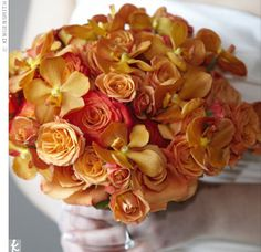 Keeping orange as her central color, the bouquet had a variety of orange roses and rusty orange Nora orchids. The stems were wrapped with ivory satin and accented with pearls throughout.