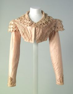 Pink silk spencer with front opening and turn down collar, applied decoration of pink satin rouleaux loops with 5 rouleaux strips at wrist and 2 rows at lower edge, collar piped in silk, 3 layers of `leaf' decoration on epaulettes over straight sleeves; c.1815. MT.2043 hand stitched collar: hand stitched lining Dimensions: Length: 300 mm (CB) Length: 160 mm (CF) Width: 350 mm (chest)