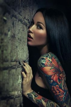 the whole picture, the girl, her lips, and make up, her hair, colors in the tattoo, the light on the cement wall...