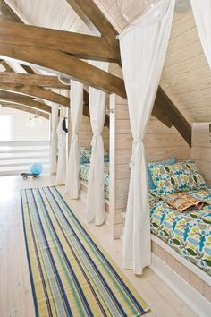 Children's Loft - Colorful Coastal Bedrooms - Southernliving. The architects designed a row of three built-in beds on the third floor loft, each lit with a marine-style sconce and closed off with curtains. Storage areas for the bunks line up across the hall, with a cubby and a drawer for each bed. The colorful bedspreads and rug add color and vibrancy to the space.  View the full home tour.