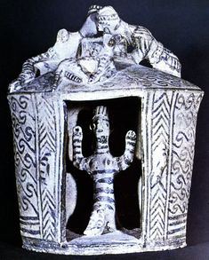 Clay shrine painted with spiralling key pattern and chevrons, with goddess or priestess inside. On the roof a couple makes love beside a cat. Arkhanes, Crete, c. 1100.