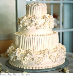 Stacked layers of buttercream-frosted wedding cake is given a fancy, stylish look by creating modern vertical lines and floral motifs.