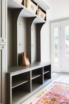 Stunning mudroom features gray beadboard lockers lined with brass hooks over a mudroom bench fitted with stacked open cubbies used as shoe shelves. Design: Alyssa Rosenheck
