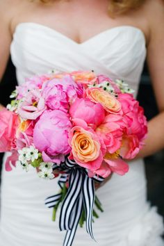 Pretty pink, coral, and peach bouquet with black and white striped ribbon.