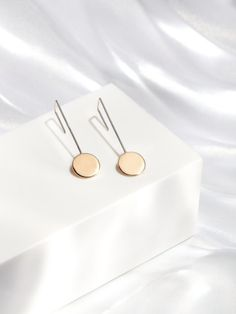 Mixed metal hand fabricated earrings featuring a solid brass circle and sterling silver ear wire. Available in all sterling silver.  Length: 1.75  Circle: .5