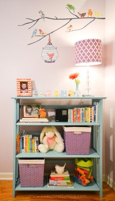Love the pops of purple in this beautifully styled bookcase in the nursery.