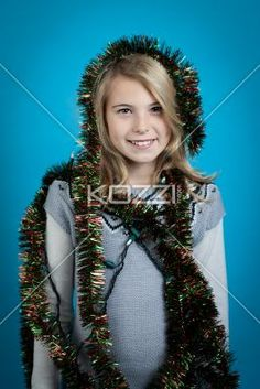girl smiling while wrapped in tinsel - Girl wrapped in Christmas decorations isolated on blue. Model: Shania Chapman - Agent is Breann at MMG. breann@nymmg.com