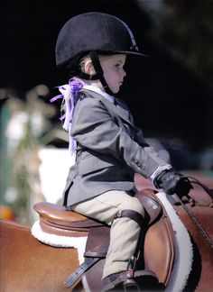 such a serious face ♥ i'd love to see the horse she is sitting on.