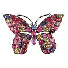 PAPILLION.  18K Yellow gold, precious spinell sapphire and diamond butterfly brooch, 24 carats red spinelles ,23.95 carats of pink, yellow and blue sapphires accented with 1.51 carats of diamonds. Black rhodium finish.
