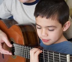 This is an image of a boy who seems to be learning to play guitar for the first time. This motivates me to develop and master my musical skills. The boy seems to be focused and intrigued by what he sees and hears. It is easy to lose that kind of passion as I get better and better. This image motivates me to always be inspired to learn more about music.