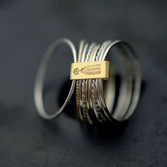 9 twist and turn silver with 14kt yellow gold stacking rings. €200.00, via Etsy.