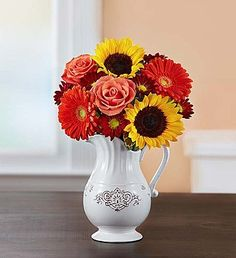 gerbera daisies, roses, sunflowers, daisies, in a white ceramic pitcher