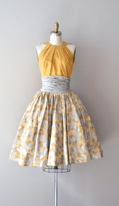stunning and rare vintage 1950s Estévez silk dress with mustard silk halter bodice, wide dove gray silk cummerbund nipped waist, very full silk gray and mustard yellow abstract print skirt and metal back zipper. --- M E A S U R E M E N T S --- fits like: xs/small bust: 32-33 waist: 25-25 hip: free length: 42.5 brand/maker: Estevez for Grenelle condition: some faint small stains on the bodice, see close up in the last photo also, a 1/8 repair near the mid-back zipper. ✈ NOTE: this i...