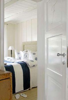 PASSER INN.Tak og gulv på dette soverommet er malt i to forskjellige hvitfarger, mens gulvet er i trehvitt. Sengeteppet er i marinestil med blå- og hvite striper, fra Home & Cottage.