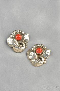 Pair of Sterling Silver and Coral Brooches, Georg Jensen, each flower set with a coral cabochon, lg. 1 1/4 in., no. 71, signed Georg Jensen, Denmark.