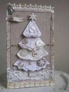 Sapin de Noël fait en napperons de dentelle en papier pliés et orné de boutons. Il est collé sur un morceau de tissu effrangé et cousu. De la pâte de texture imite de la neige. Le sapin et la neige sont recouvert de glitter et saupoudré de paillettes.