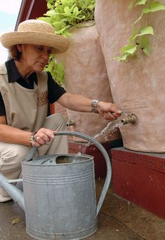 woman filling rain barrel from spigot outside