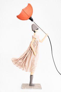 Queste bellissime lampade da tavolo sono realizzate a mano da Xenia, una geniale artista Greca. Ogni lampada è contraddistinta dal suo nome e dal suo abito. Il corpo è realizzato in legno e il vestito con tessuti riciclati e inamidati per mantenere la forma come in foto (effetto vento). Altezza: circa 85cm