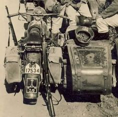 Soldiers pausing with their motorcycle