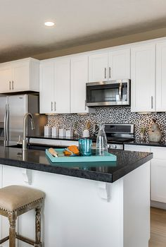 Black countertops and white cupboards make the optimal contrast. Beautiful home design ideas from Candlelight Homes.