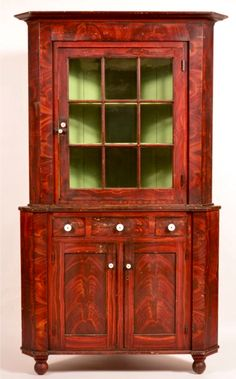 "Conestoga Auctions -  Harry B. Hartman Estate Auction - Session II  May 16, 2015.  Lot 680.    Estimate: $3,000 - $5,000.  Realized: $6,050.    Description:  York County, PA Federal Grain Paint Decorated Softwood Two-Part Corner Cupboard. A ttributed to John Rupp, Hanover, Pa. Bold grain painted decoration, stepped cornice with single glazed nine pane door above a stepped base with three split dovetailed drawers, two lower paneled doors, molded base and turned feet. 85-1/2""h x 48""w x 22""d…"