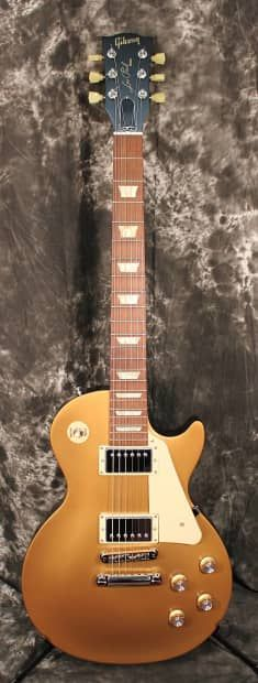 2012 Gibson Les Paul Studio Goldtop Electric Guitar w/ non original Gigbag. Excellent +++ condition, one very minor mark on the back of the neck and one very minor mark near the neck pickup. Otherwise, Absolutely perfect condition! No fretwear, plays very low and smooth and it has that Gibson sound. Released midway through 2010, the Les Paul Studio '50s Tribute packed the stripped-down appeal of the long-running Studio line in a great '50s-themed model with P-90 pickups that was a major…
