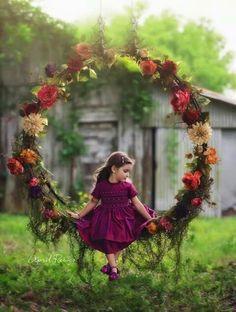 Small child sitting/swinging on swing of flowers